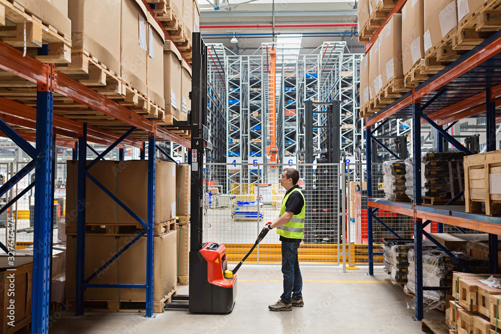 Fototapeta Storehouse employee in uniform working on forklift in modern automatic warehouse. Boxes are on the shelves of the warehouse. Warehousing, machinery concept. Logistics in stock.