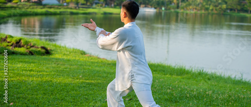 Obraz Young man practicing traditional Tai Chi Chuan, Tai Ji and Qi gong in the park for healthy, traditional Chinese martial arts concept. - fototapety do salonu