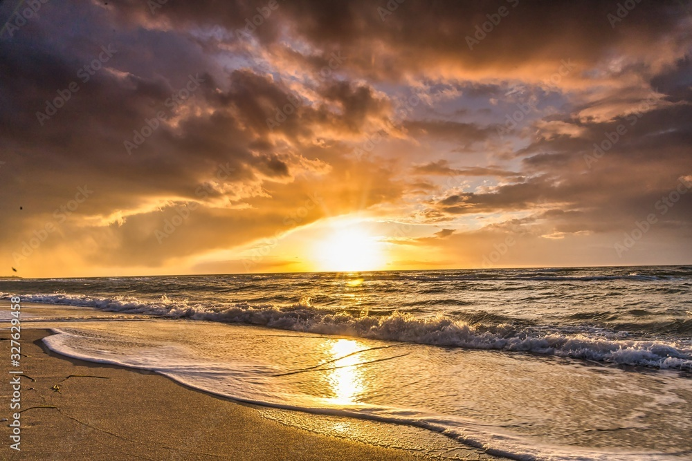 Fototapeta  colored sunset with cloud cover over the sunset at the beach - dramatic sunset on the baltic sea
