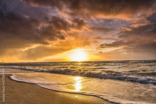 colored sunset with cloud cover over the sunset at the beach - dramatic sunset on the baltic sea