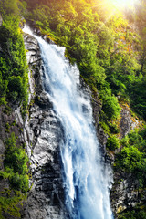 Panel Szklany Wodospad Panoramic beautiful deep forest waterfall in norway near blue ocean. Waterfalls mountain view close up.
