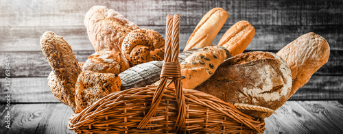 Tela Various bread with wheat on old table in wooden wicker basket