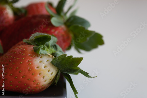 strawberries on gray ceramic plate with white background