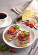 Lunch. Sandwiches with sausage and a cup of coffee on a light grey background. Tomatoes, garlic, white bread, parsley, knife and spices. Background image, copy space
