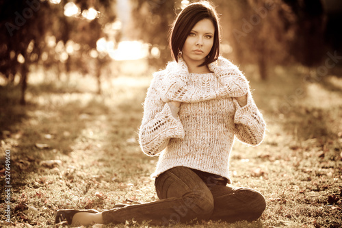 Photo Monochrome photo of a pretty serious young woman in casual clothes sitting on a lawn in a park on sunny autumn warm day