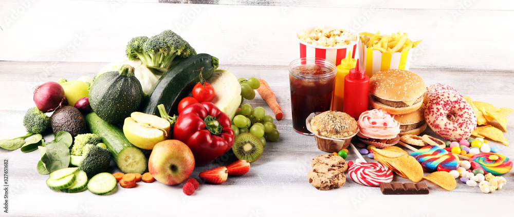 Fototapeta healthy or unhealthy food. Concept photo of healthy and unhealthy food. Fruits and vegetables vs donuts,sweets and burgers