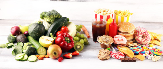 healthy or unhealthy food. Concept photo of healthy and unhealthy food. Fruits and vegetables vs donuts,sweets and burgers