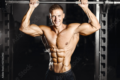 Bodybuilder strong man pumping up abs muscles Wallpaper Mural
