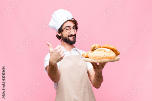 Obraz na plátně young crazy baker man holding bread against pink wall