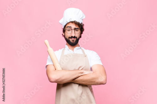 Fotografía young crazy baker man with a cook tool against pink wall