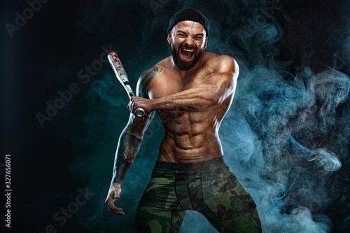 Strong and fit man bodybuilder with baseball bat shows abdominal muscles under a t-shirt Tablou Canvas