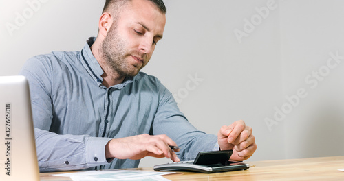 Obraz Businessman filling 1040 individual tax form with calculator at office desk. - fototapety do salonu