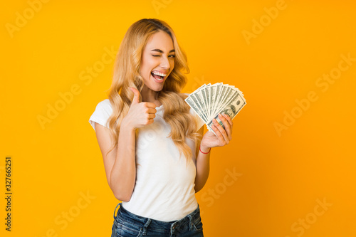Fototapeta Cashback. Excited woman holding money banknotes and showing thumb up obraz