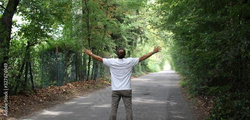 Valokuvatapetti Uomo felice e libero sul viale alberato in primavera