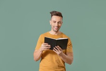 Young Man Reading Book On Color Background
