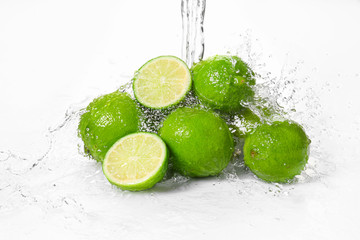 Water pouring on fresh limes against white background
