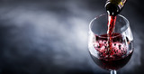 Pouring glass of red wine from a bottle in wide banner shape or copy space for text..