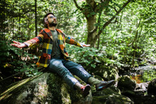 A Young Bearded Male Is Sitting On The Stone In The Forest And Enjoying Nature. A Man Looking Up With Opened Widely Arms And Dreaming