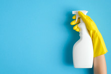Hand In A Yellow Rubber Glove Holds Cleaner Spray Bottle Over Blue Background. Cleaning Service Banner Mockup. Housecleaning And Housekeeping Concept. Flat Lay, Top View