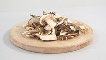 Lot Of Slices Of Dry Brown Mushroom Boletus Edulis On A Wooden Round Pad