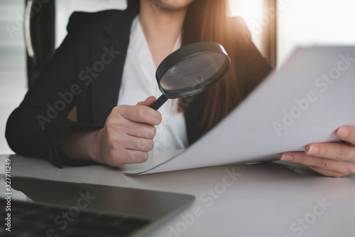Photo Business woman using magnifying to review balance sheet annual