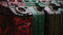 A Few Large, Old Metal Cans  To Fill With Fuel Lined Up Next To Eachother Full Of Rest And In Red, Green And Brown
