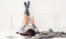 Young Woman Relaxing Reading Book And Drinking Cup Of Hot Coffee Or Tea  On Bed At Home