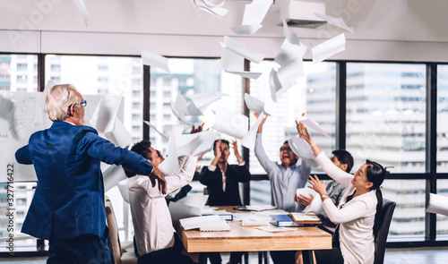 Successful group of casual business relaxing and throwing paper in modern work loft.Creative business people celebrating with arms up.Teamwork and success concept