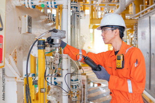 Instrument technician operator calibrate pressure transmitter with hand held calibrator on offshore oil and gas central processing platform Fototapet