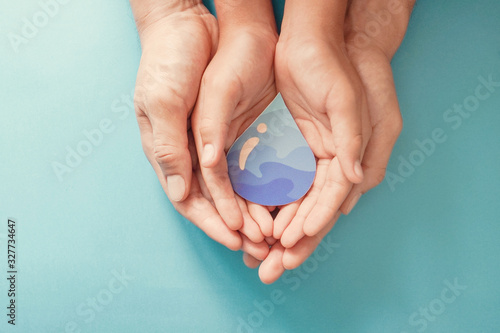 Adult and child hands holding paper cut water drop, World Water Day, Clean water and sanitation, hand sanitizer, family washing hands, CSR, save water, ecology concept
