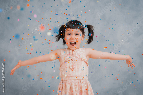 Obraz little girl child cheerfully throws up colorful tinsel and confetti on a gray blue background. - fototapety do salonu
