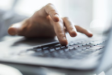 Male Hands Typing On Laptop Keyboard In Sunny Office, Business And Technology Concept. Close Up