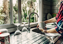 A Woman Washes Dishes In Her H...