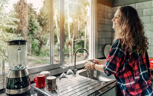 Fototapeta A woman washes dishes in her house, a sink in front of a window overlooking a summer garden obraz