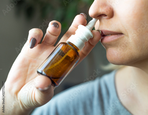 Woman using nasal spray close up. Health care concept. Canvas Print