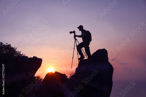 Obraz Photographer climbing on the top of the mountain to take a picture at sunset. - fototapety do salonu