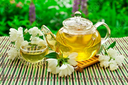 Photo Jasmine green tea in a glass teapot with a glass cup and fresh blossoms