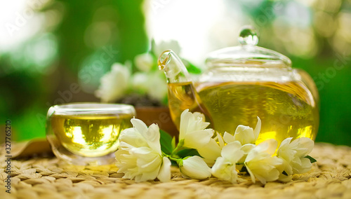 Jasmine green tea in a glass teapot with a glass cup and fresh blossoms Canvas Print