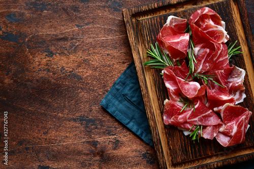 Fototapeta Slices of prosciutto di parma or jamon serrano (iberico) . Top view with copy space. obraz