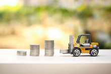 Miniature Forklift Loading Money Coins And The Growth Pile Of Money Coins ,bokeh Background..