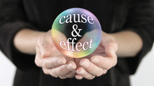 Nothing Escapes Cause And Effect - Female With Cupped Hands And A Rainbow Coloured Transparent Bubble Containing The Words CAUSE & EFFECT