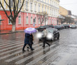 Busy city street people on zebra crossing in a rainy day. Dangerous situation. Defocused image