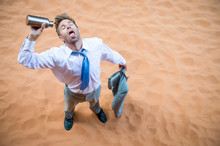 Thirsty Businessman Standing On Red Sand Desert Pouring An Empty Water Bottle Over His Tongue