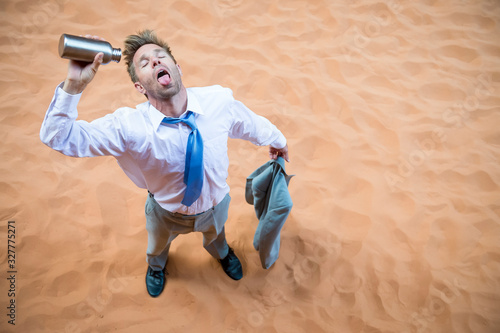 Valokuva Thirsty businessman standing on red sand desert pouring an empty water bottle ov