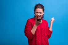 Emotional Portrait Of Brunette Caucasian Pretty Woman With Evening Make Up And Curly Ponytail. She Wears Red Sweater And Poses On Blue Background With Her Phone, Being Angry. Copy Space