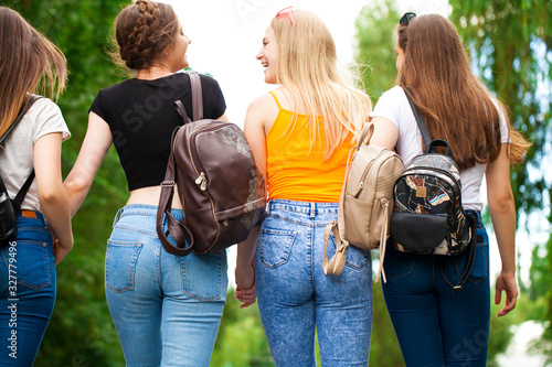 Photo Four happy schoolgirls walking in summer park
