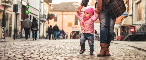 Fotografiet horizontal background of mother helping his baby to do first steps walking
