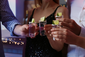 Young people toasting with Mexican Tequila shots in bar, closeup