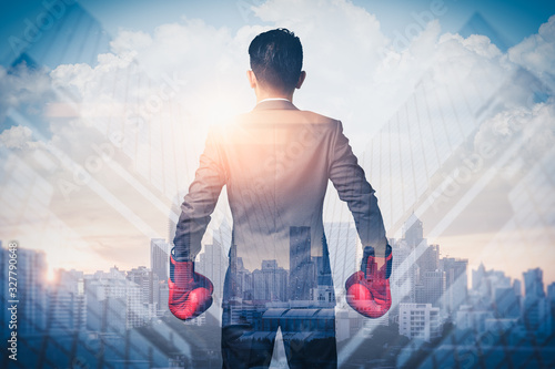 the double exposure image of the businessman wearing a boxing mitts overlay with cityscape image Wallpaper Mural