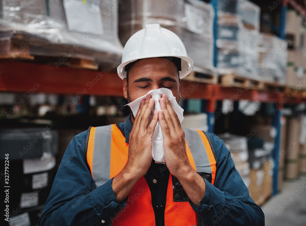 Fototapeta Young african manager coughing and feeling sick while covering mouth with handkerchief in warehouse